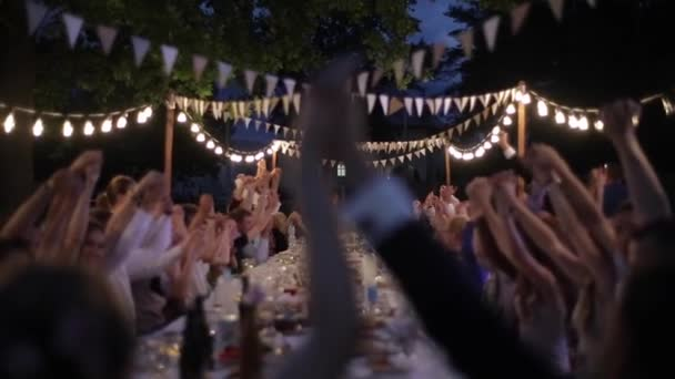Belarus, Minsk - May 30, 2018: Outdoor wedding feast with retro garland. People at the table. Wedding banquet. Night time. Wedding setup. Bride and groom having funwith guests.