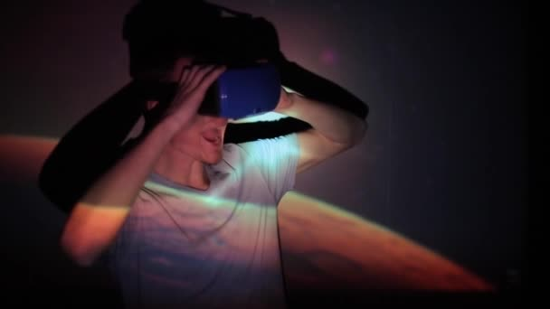 Minsk, Belarus - 11 June 2019: Handsome caucasian man wearing virtual reality headset with amazing cosmic futuristic space virtual imaging on background. Guy is enjoying the view