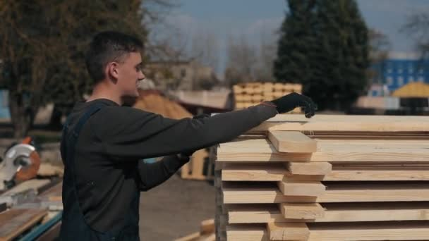 Man folds wooden planks. Stacks of square wood planks for furniture materials.