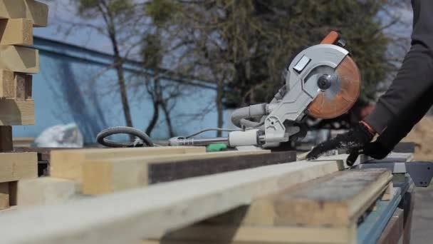 Close up of wood cutting machine cuts plank. Worker cuts wooden boards.