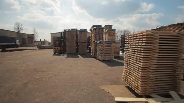 Targonca üzemeltető a raktárban fa raklapokat kezelni. Ember használ Loader Dor Pack fából készült deszka.