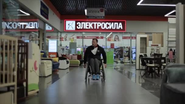 Bobruisk, Belarus - 11 May 2019: disabled person rides in a wheelchair at the shopping center.