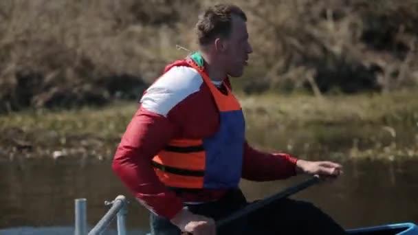 Nahaufnahme Porträt eines Athleten, der im Kanu auf dem Fluss rudert. Rudern, Kanufahren, Paddeln. Ausbildung. Kajakfahren. Mann fährt gegen Brücke. Kamerafahrt
