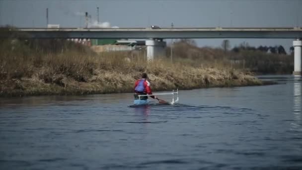 Disabled man rowing on the river in a canoe. Rowing, canoeing, paddling. Training. Kayaking. paraolympic sport. Bridge on the background.