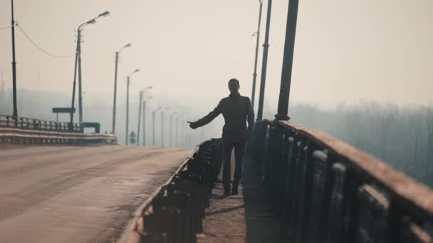 A young man is hitchhiking. The man is trying to catch a passing car for traveling. Guy walking on the bridge. Cars go on the road. Morning and fog. Spring.