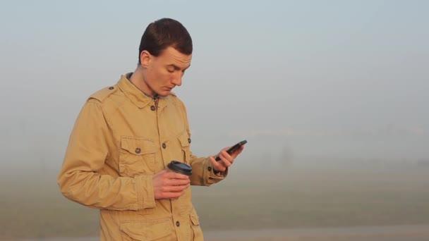 Naht den Menschen im Freien mit dem Handy auf und scrollt das Band. Mann trinkt Kaffee und telefoniert.