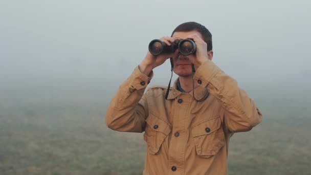 Close up of Young redhead man in khaki coat holding a binoculars looking sunrise and sunset on background. Fog around him.