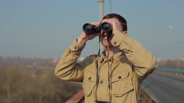 Fiatal férfi vörös hajú a khaki kabát keres keresztül távcsövet a hídról.