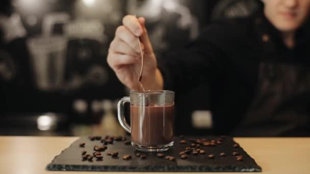 Barkeeper, der heiße Schokolade zubereitet, gießt sie aus einem Löffel in eine Glasschale. Nahaufnahme