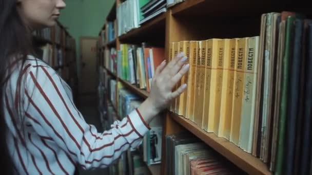 Bobruisk, Bělorusko-11. duben 2019: zavření rukou chytrá a krásná mladá dívka v bílé košili a brýle ve školní knihovně výběr knihy ke čtení