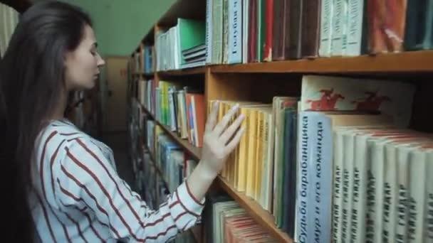 Zavři ruce chytrá a krásná mladá dívka v bílé košili a brýle ve školní knihovně výběr knihy ke čtení