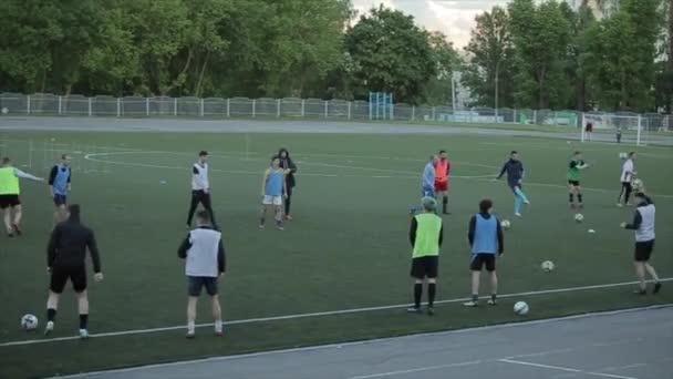 Die Spieler des Fußballklubs trainieren und machen eine Übung über die Geschwindigkeit und Genauigkeit der Übertragung der Fußbälle. Nahaufnahme. Modell realisiert