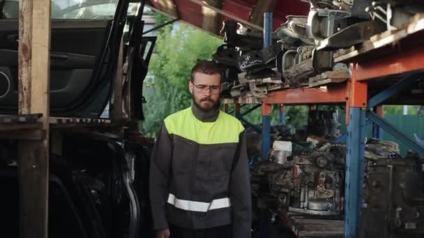 Mladý vousatý automechanik s brýlemi kráčí mezi regály náhradních dílů a zastavuje se s rukama založenýma na prsou. Detailní záběr. Zpomalený pohyb