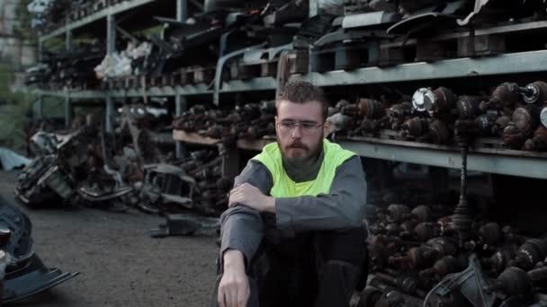 Mladý vousatý mechanik v brýlích a v šedých kombinézách sedí a kouří ve skladu náhradních dílů opravny aut. Detailní záběr