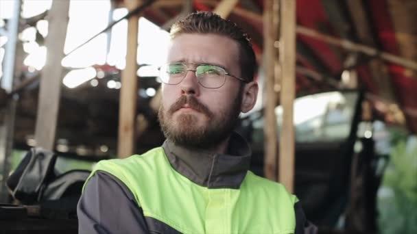 Mladý vousatý dělník opravny aut v brýlích stojí na pozadí regálů a těžce vzdychá. Detailní záběr