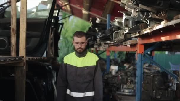 Vážný mladý vousatý automechanik v uniformě stojí s rukama založenýma na prsou na policích s náhradními díly. Detailní záběr