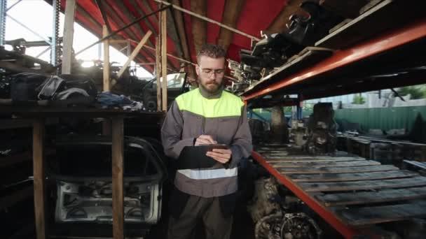 Mladý unavený vousatý automechanik s brýlemi těžce vzdychá, zatímco si dělá poznámky do zápisníku ve skladu náhradních dílů. Zpomal. Detailní záběr