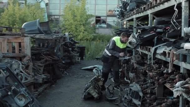 Mladý automechanik v šedých kombinézách kráčí pod baldachýnem s policemi s náhradními díly a dělá si poznámky do sešitu