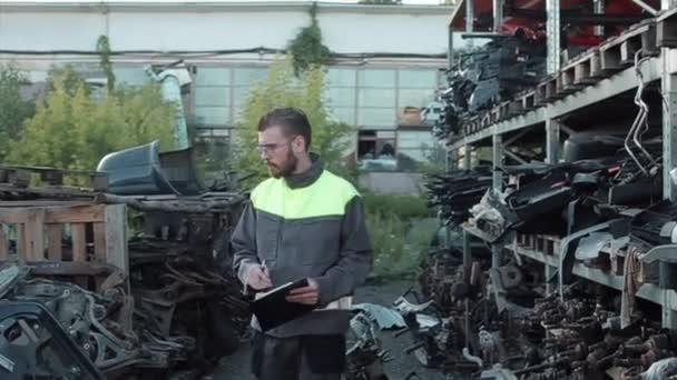 Mladý mechanik v šedé uniformě z opravny sleduje náhradní díly pro auta a zapisuje data do sešitu
