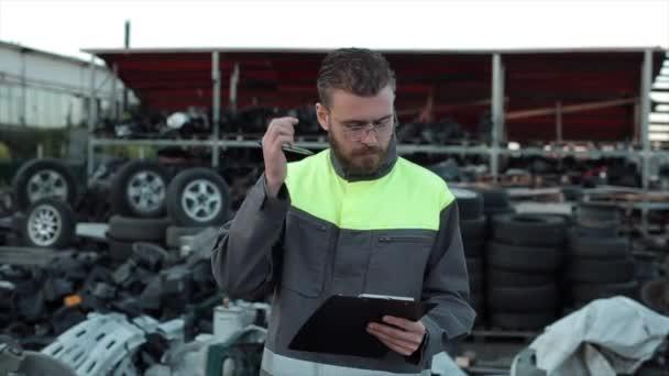 Mladý mechanik s brýlemi stojí mezi náhradními díly na dvoře autoservisu, za uchem si bere pero a dělá si poznámky do zápisníku. Detailní záběr