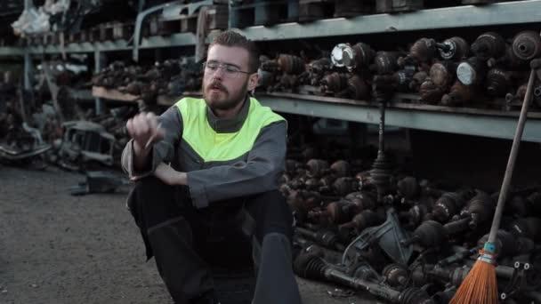 Mladý vousatý mechanik v montérkách a brýlích kouří v autoopravně na pozadí regálů s náhradními díly
