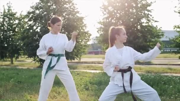 Két fiatal lány fehér kimonóban szinkronban demonstrálja a harcművészeti technikákat a karate edzés alatt. Előre nézz. Közelkép