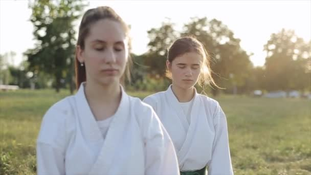 Young women in white kimono practice karate meditate while sitting on the grass and bow. Front view. Close-up. Slow motion. Blurred background