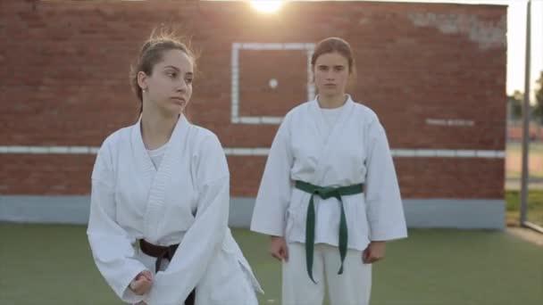 Két női sportoló karate edzésen a sportpályán gyakorolja a technikát és szinkronizált gyakorlatokat végez. Előre nézz. Közelkép. Lassú mozgás.