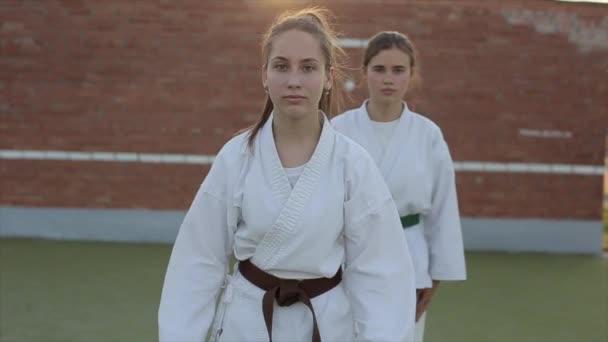 Két fiatal nő bemutatja a kyokushinkai technikákat a karate edzésen a sportpályán. Előre nézz. Közelkép. Lassú mozgás.