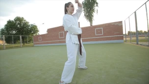 Karate-Mädchen im weißen Kimono auf dem Sportplatz zeigen Karate-Techniken und machen einen Sprung mit einer Drehung. Nahaufnahme. Unterer Schusswinkel. Zeitlupe