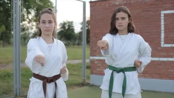 Két fiatal nő karate edzést tart egy sportpályán, és bemutatják a technika különböző pózait kyokushinkai. Előre nézz. Közelkép