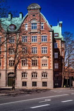 beautiful old building with large windows and decorations on empty street in copenhagen, denmark