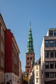 Fotografie old tower with tall spire and historical buildings on street in copenhagen, denmark