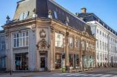 Fotografie beautiful historical building with large windows and decorative sculptures on street in copenhagen, denmark