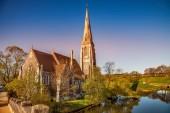 Fotografie calm pond with green vegetation near beautiful old church at sunny day, copenhagen, denmark