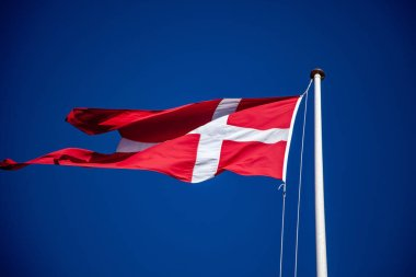 Low angle view of flag of denmark waving against blue sky stock vector