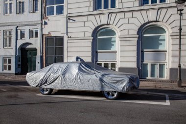 parked car covered with tent on empty street with historical buildings in copenhagen, denmark