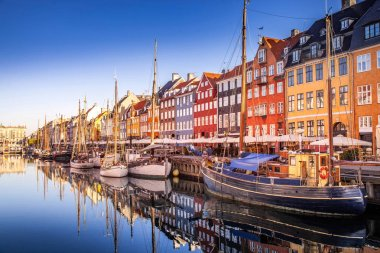 COPENHAGEN, DENMARK - MAY 6, 2018: picturesque view of historical buildings and moored boats reflected in calm water, copenhagen, denmark
