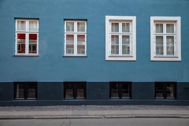 detail of blue and grey building with white windows on street in copenhagen, denmark