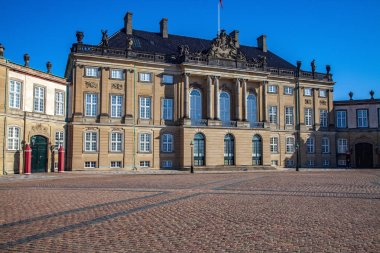 Amalienborg palace on empty street and historical building with statues and columns in copenhagen, denmark