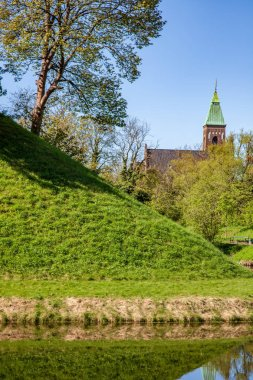 green hill and trees reflected in calm water and beautiful old palace behind, copenhagen, denmark