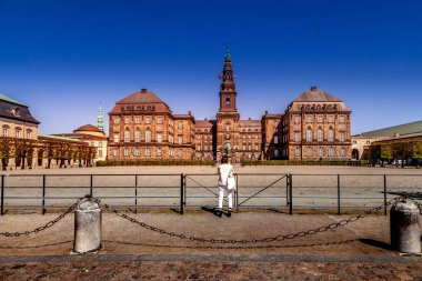 COPENHAGEN, DENMARK - MAY 6, 2018: rear view of woman taking picture of Christiansborg palace