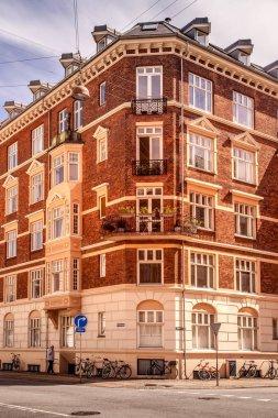 COPENHAGEN, DENMARK - MAY 6, 2018: man walking on street and bicycles standing near building in Copenhagen, Denmark stock vector