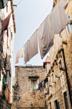 low angle view of laundry and empty narrow city street in Dubrovnik, Croatia