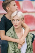 Photo beautiful preteen boy hugging mother while sitting together on stadium