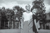 Fotografie black and white photo of mother and son looking away while standing back to back in park