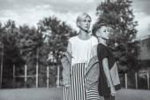 Fotografie černo-bílé fotografie matky a syna v uhýbaje stoje zády k sobě v parku