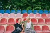 Fotografie šťastný matka a syn se vzájemně zatímco sedí spolu na stadionu sedačky