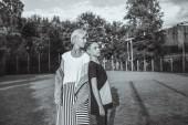 Fotografie černo-bílé fotografie matky a syna stojí zády k sobě na trávníku