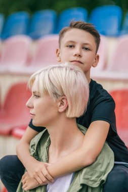 beautiful mother and son embracing while sitting together on stadium